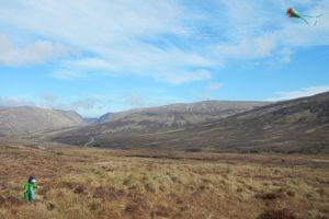 Kind mit Drachen in den schottischen Bergen