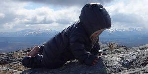 Kleines Kind im Daunenoverall krabbelt über Felsen