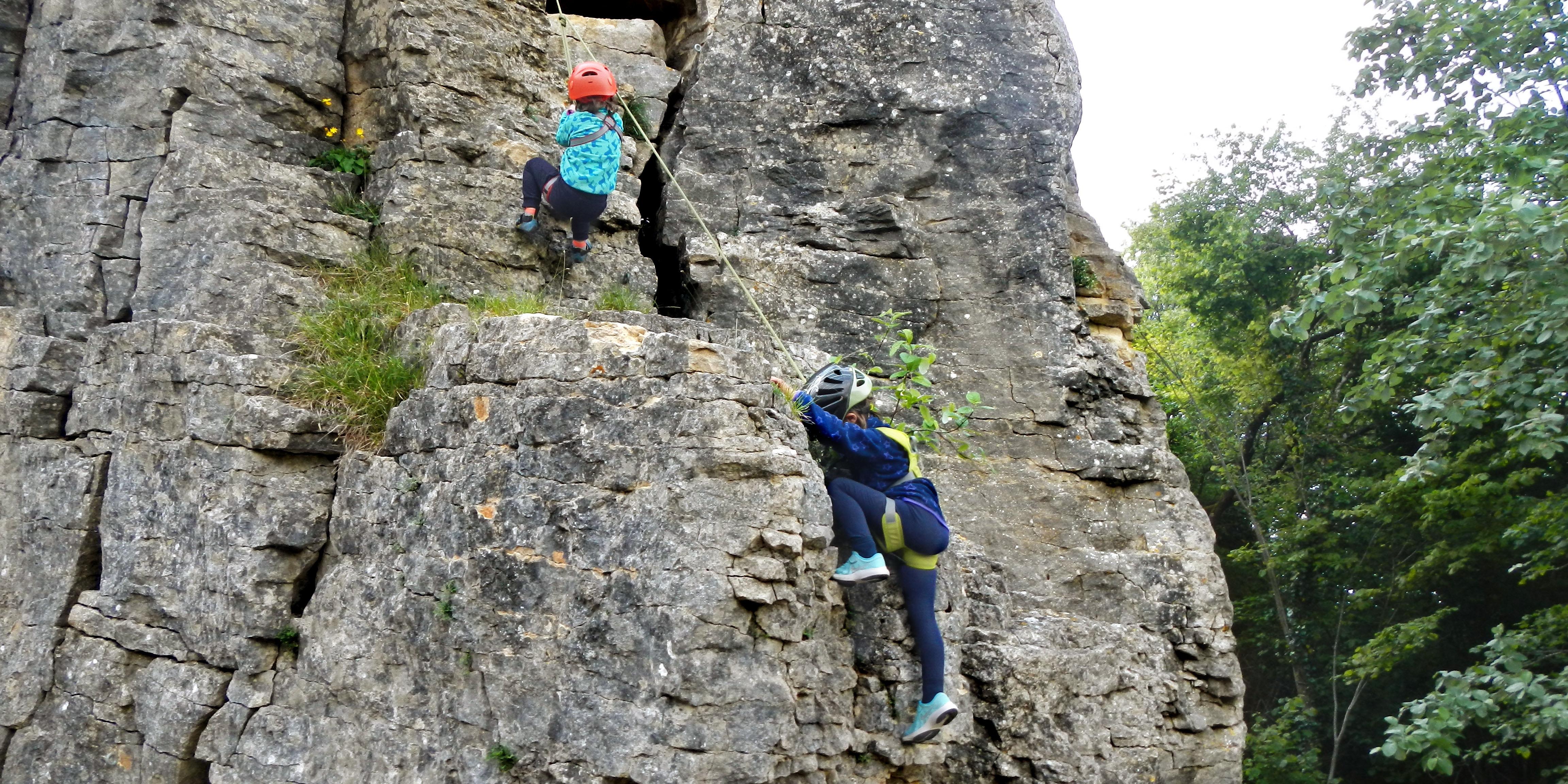 Kinder klettern am Seil auf dem Felsen