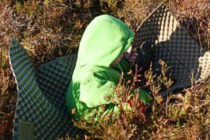 Kleines Kind auf leichter Isomatte im Heidekraut