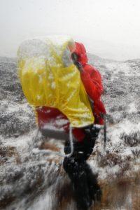 Kraxe mit Kind im Schneegestöber, wird gerade abgesetzt