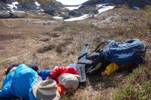 Schlafende Mutter neben schlafendem Kind und einem zweiten Kind, das in der Kraxe zugedeckt ist, in wilder Berglandschaft.