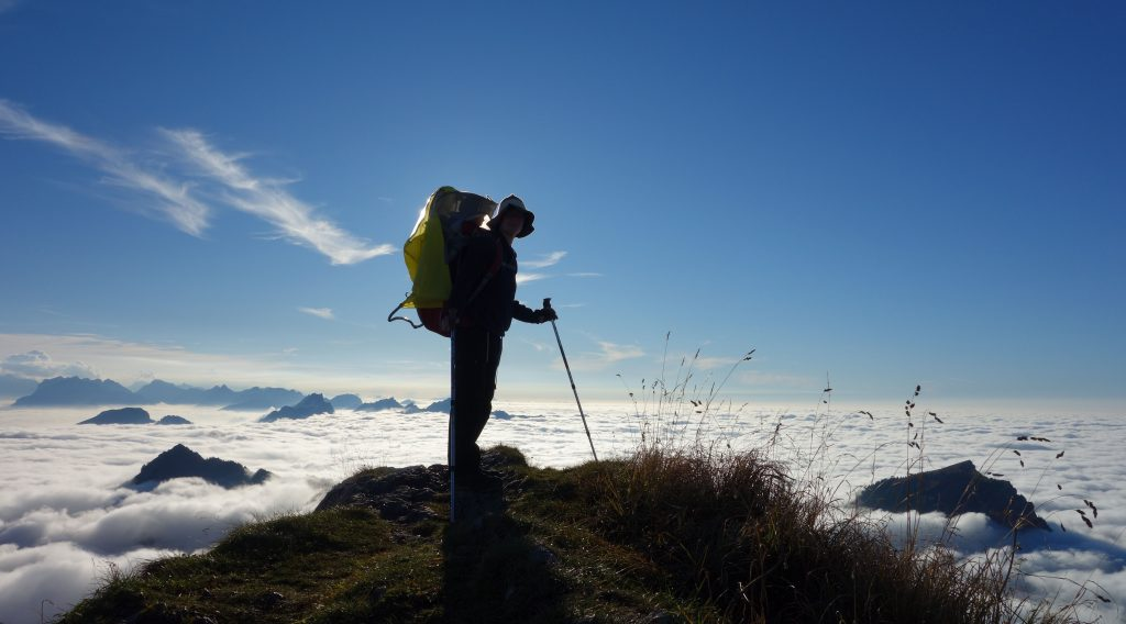 Frau mit Kraxe im Gegenlicht auf einem Berggipfel über dem Wolkenmeer