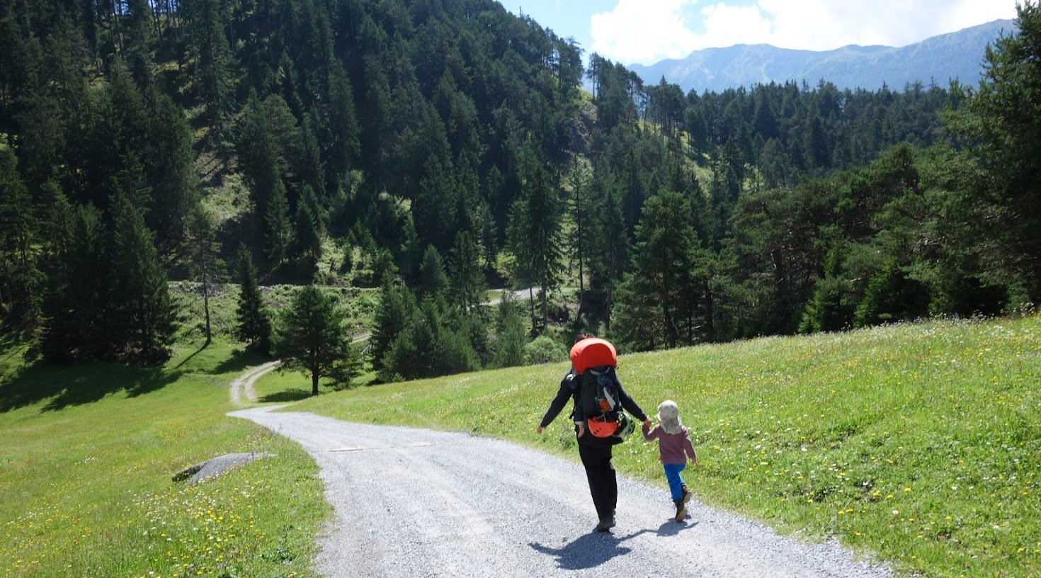 Mutter und Tochter rennen Hand in Hand einen sonnigen Feldweg hinab