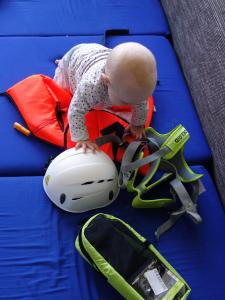 Kleines Kind beim Untersuchen von Klettergurt, Helm und Schwimmweste