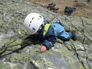 Kleinkind beim Felsklettern auf Granitplatte
