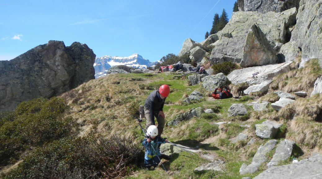 Kleines Kind und Mutter in den Bergen, mit Spielen mit Wanderstock beschäftigt