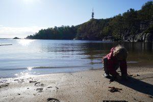 Kind am sonnigen Sandstrand in Norwegen