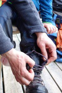 Versuch, mit dem Verschluss eines Schuhs zurechtzukommen