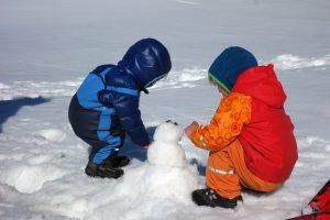Kinder beim Bau eines kleinen Schneemanns