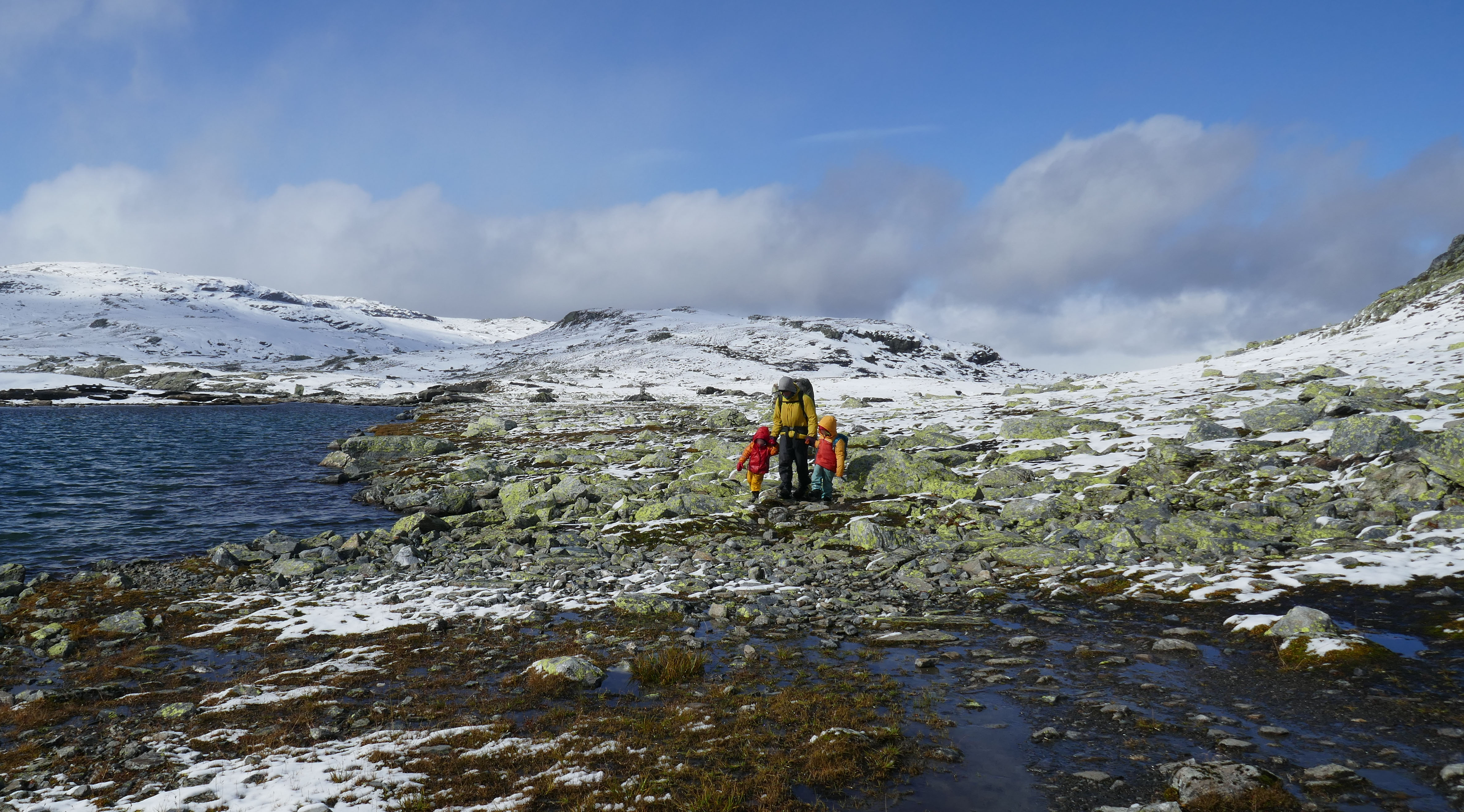 Wandern mit Kindern in Sonne und Schnee durch die Berge von Norwegen