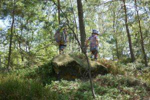 Begeisterte Kinder auf dem Weg über einen kindergerecht großen Felsen