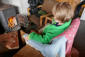 Kind vor dem Feuer, gemütlich in einer norwegischen Hütte