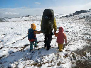 Wandern mit Kindern durch eine wundervolle norwegische Schneewelt im Sonnenschein