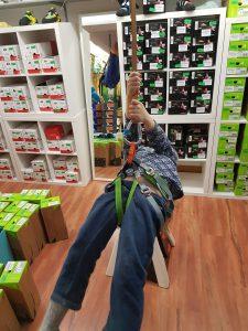 Ein Kind probiert akrobatisch, ob es schon stabil im Hüftgurt sitzen kann