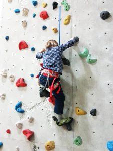 Kind klettert in der Kletterhalle mit Hüftgurt in der automatischen Selbstsicherung