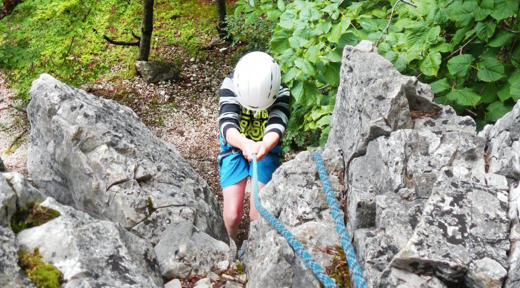 Junge mit Klettergurt wird abgeseilt durch Ablassen