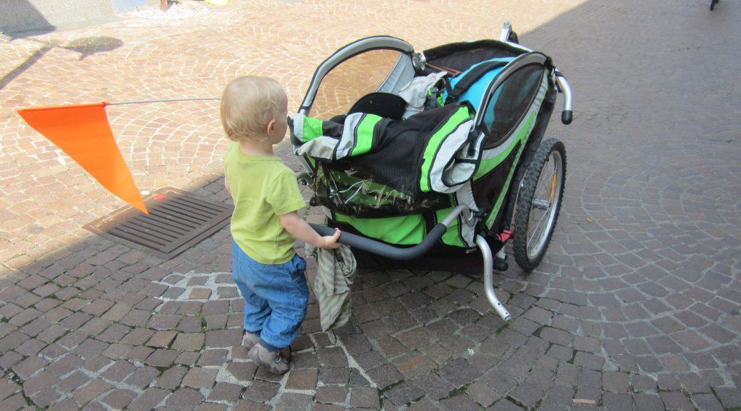 Kleines Kind schiebt seinen Fahhrradanhänger lieber selber