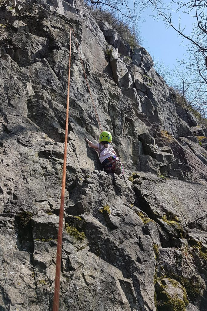 Kind klettert mit Seil gesichert am Fels