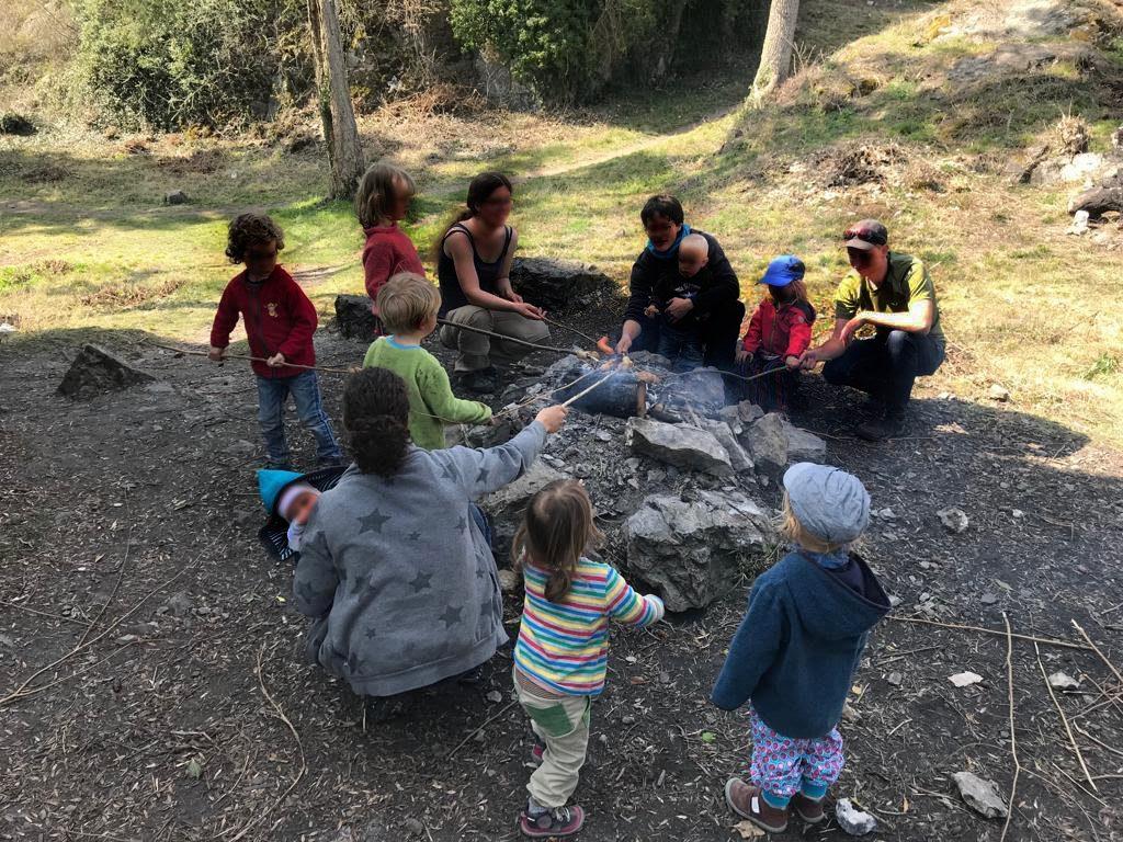 Eltern und Kinder sitzen um das Lagerfeuer herum und braten Würstchen