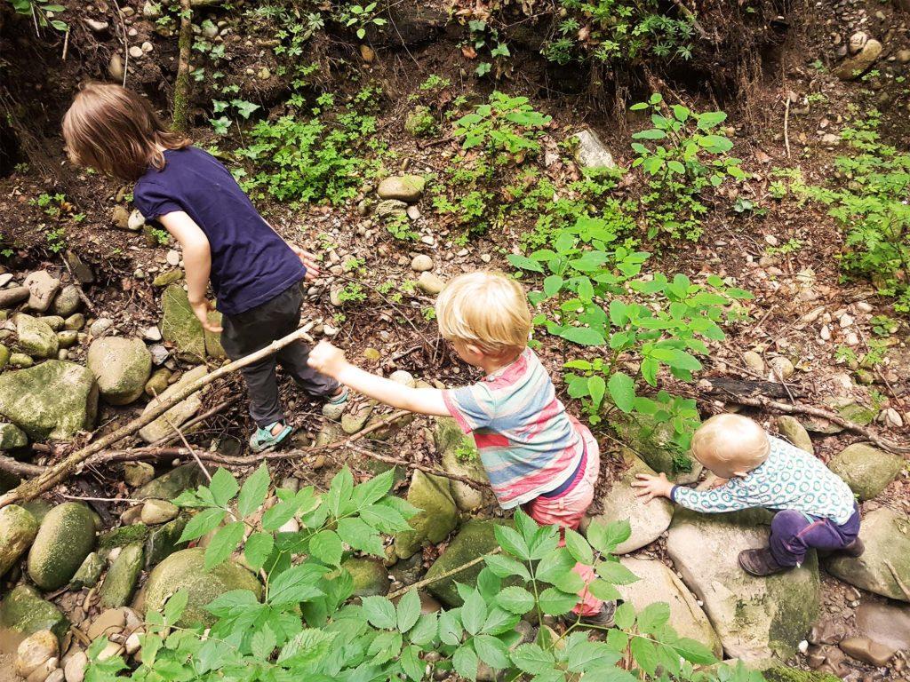 Drei kleine Abenteurer-Forscher-Kinder auf Expedition im Bachbett