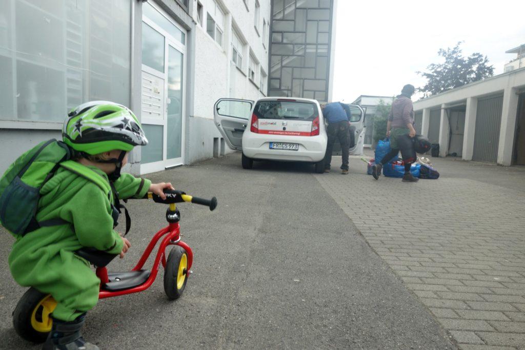Kind mit Roller und gepacktes Auto