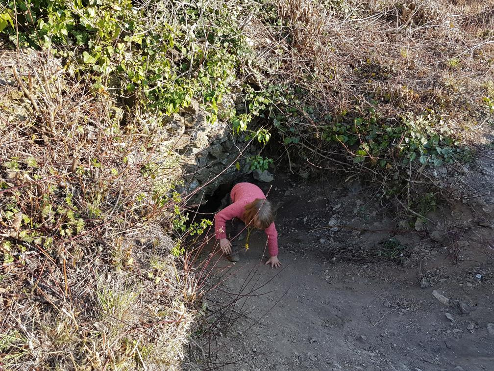 Kind erforscht ein Loch in einer alten Mauer