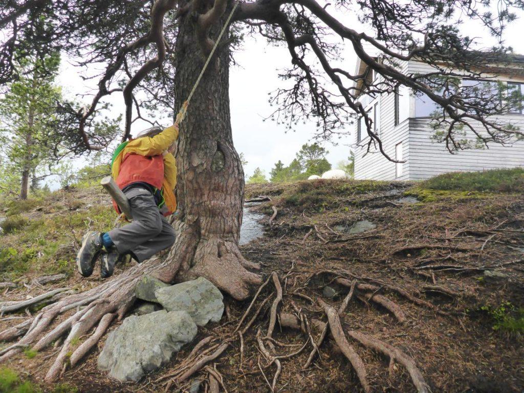 Kind auf improvisierter Schaukel vor einer Hütte