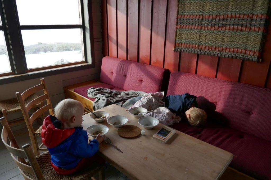 Kinder auf der Bank in einer Berghütte, Ausruhen von der mehrtägigen Hüttenwanderung