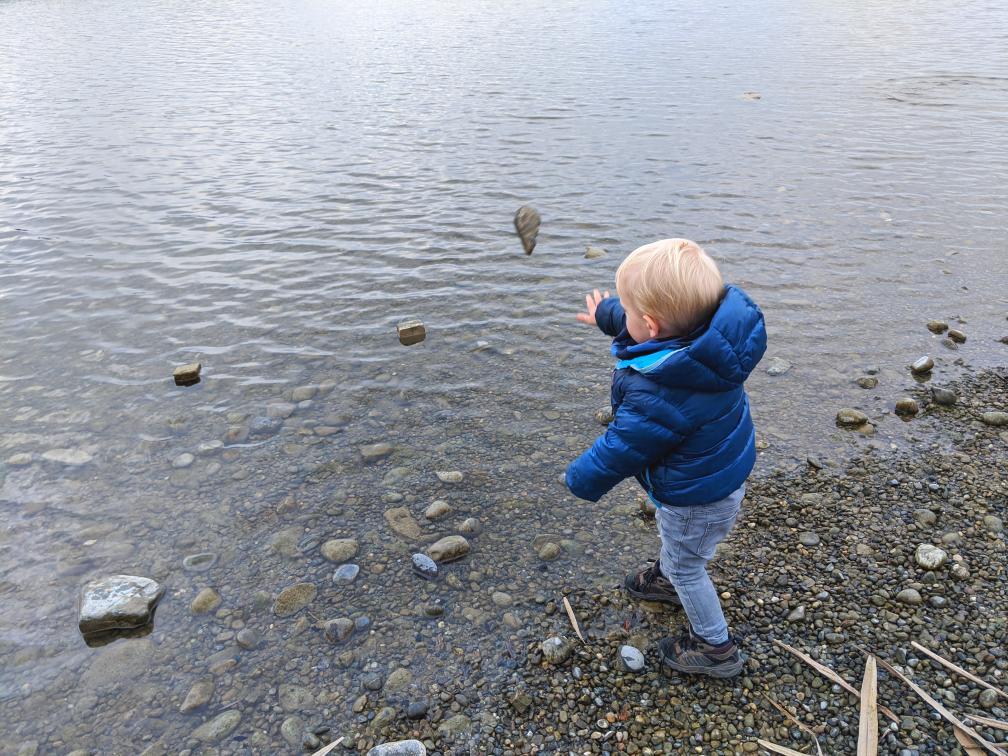 Kleines Kind wirft Stein ins Wasser
