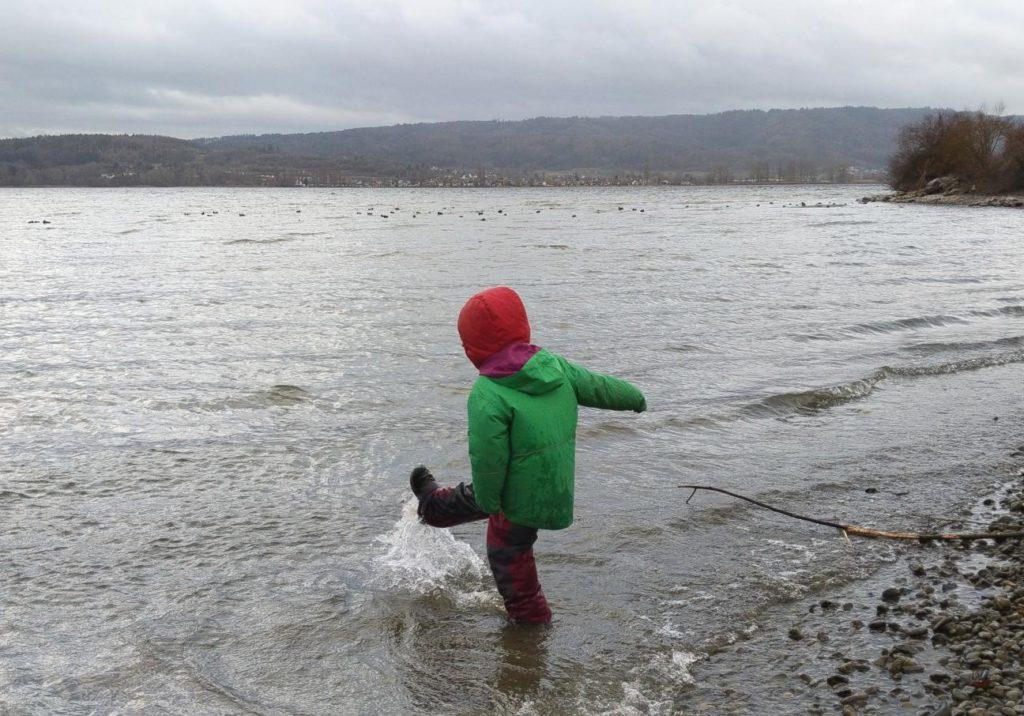 Kind kickt mit dem Fuß ins Wasser