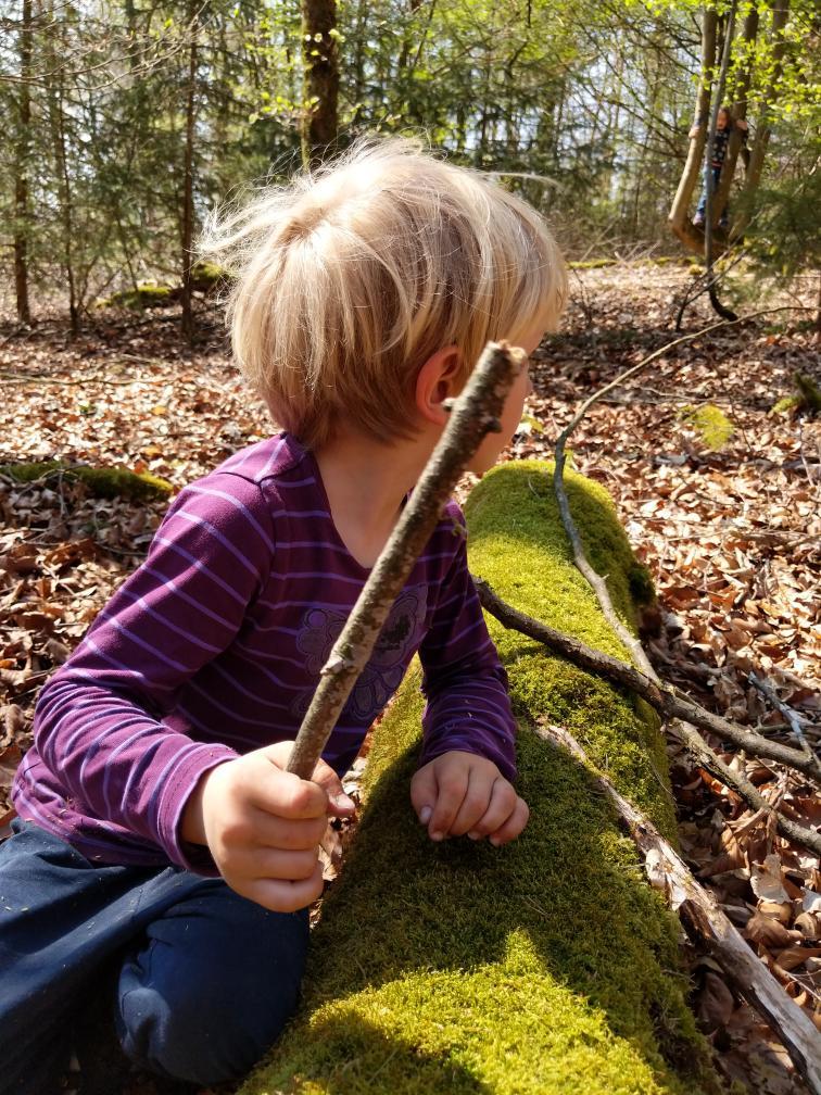 Kind lehnt an bemostem Baumstamm