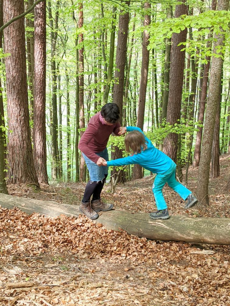 Rangeleien am Baumstamm - Kind und Mutter
