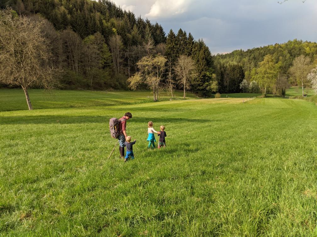Familie mit Kindern auf Wiese im Frühling