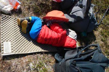 Kind schläft auf Isomatte im Heidekraut