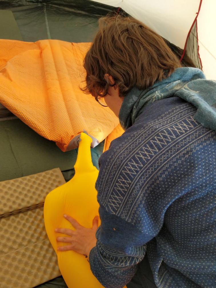 Eine moderne luftgefüllte Isomatte wird mit Pumpsack aufgepumpt