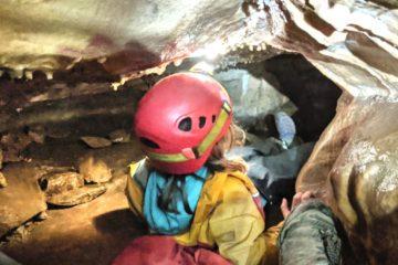 Kind in wilder Höhle, an einer Engstelle