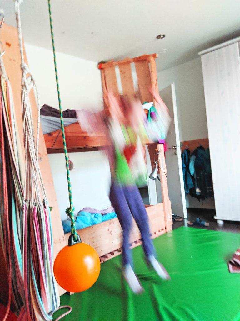 Kind hüpft vom Hochbett, daneben Boje als Schaukel