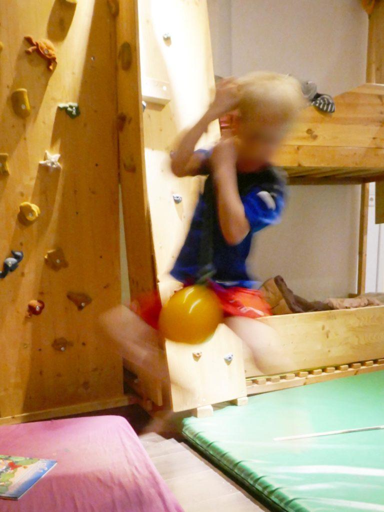 Aufspringen auf die Kugel-Schaukel, im Hintergrund Kletterwand im Kinderzimmer