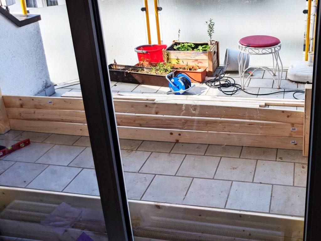 Ein Hochbeet auf dem Balkon wird gebaut, im Hintergrund eine bepflanzte Obstkiste und Blumenkästen