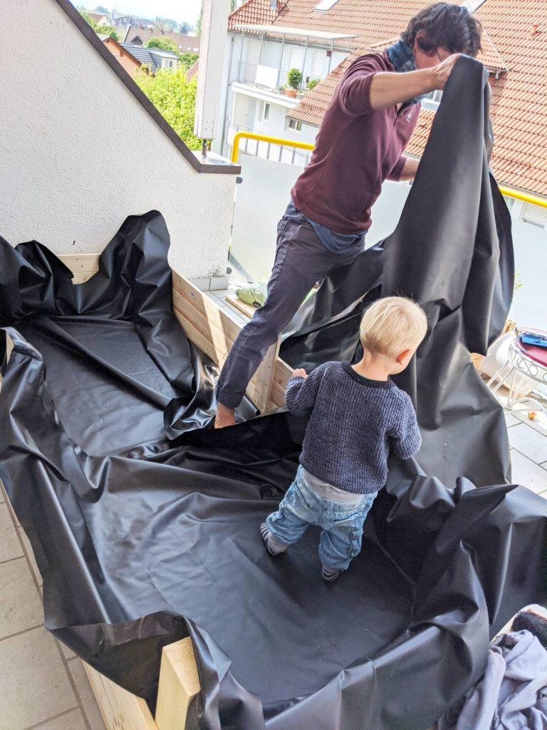 Das selbstgebaute Hochbeet auf dem Balkon wird mit Teichfolie ausgekleidet