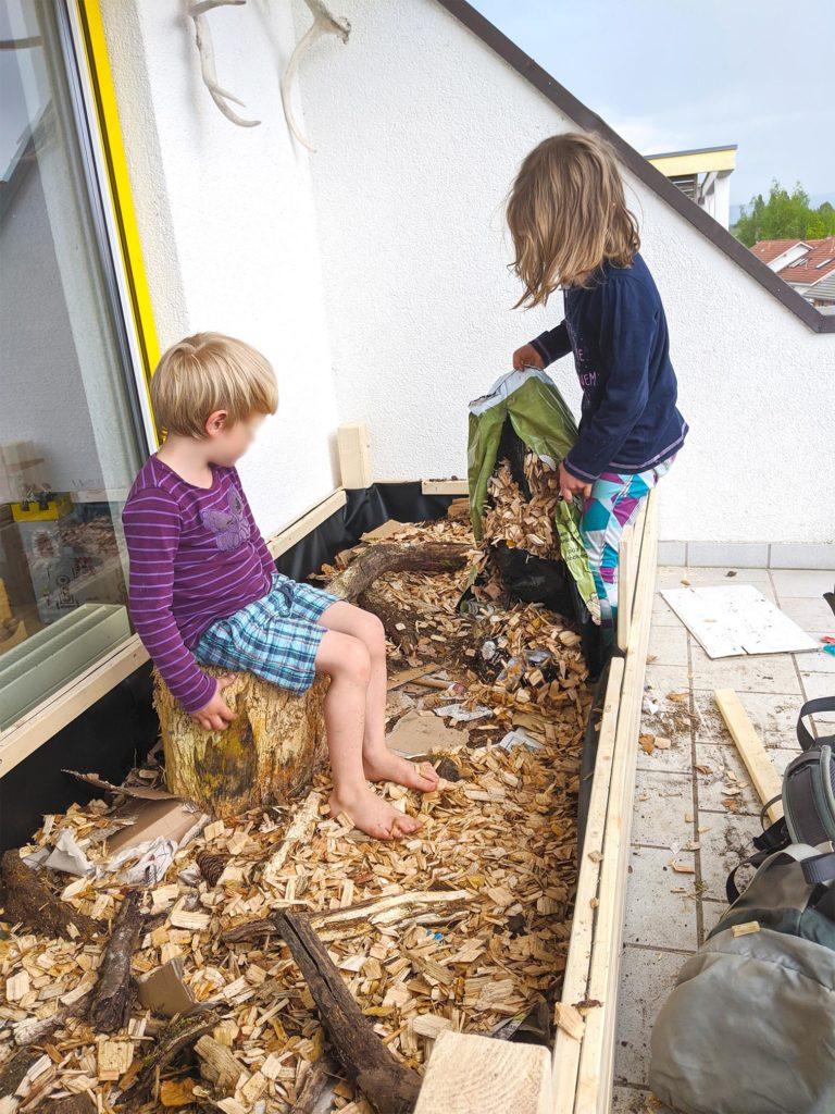 Das Hochbeet wird mit Erde befüllt - zuerst Holz-Hackschnitzel für das Wasser