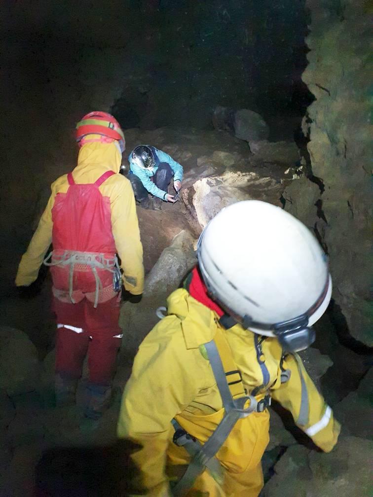 Kinder erforschen eine geräumige Halle in einer Höhle