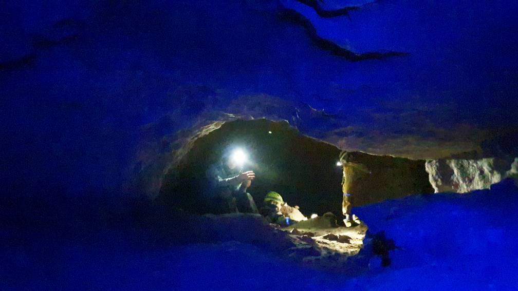 Halle in einer Höhle in mystischem blauem Licht, mit Höhlenforschern