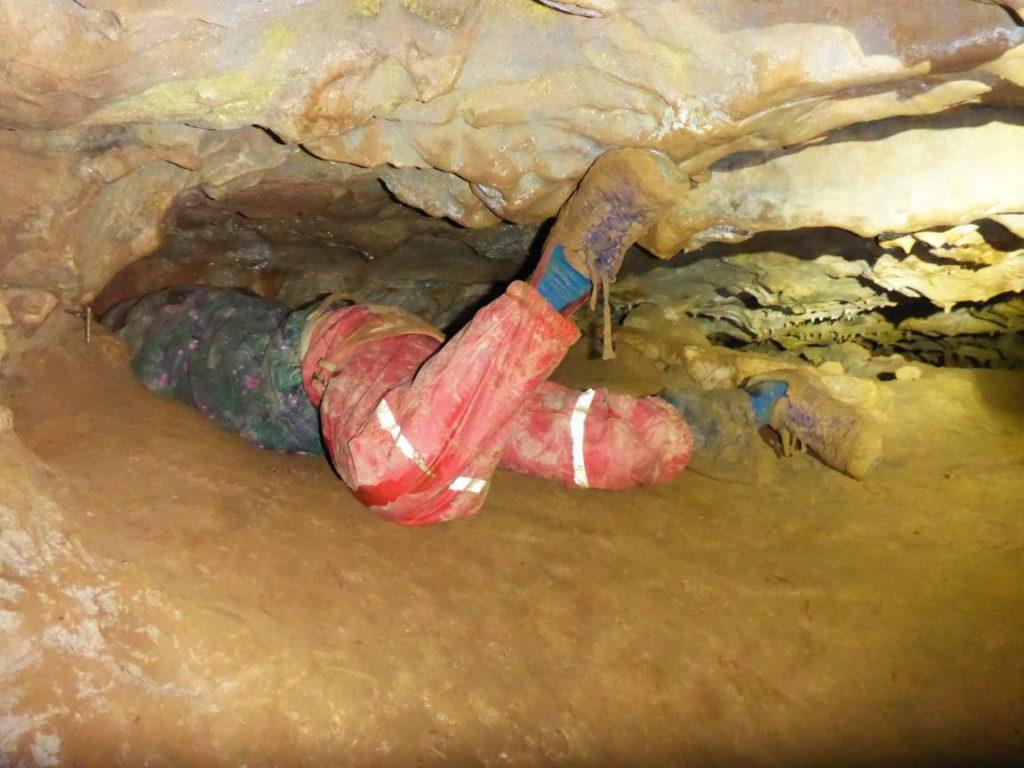 Ein Kind verschwindet im Gang einer engen Höhle