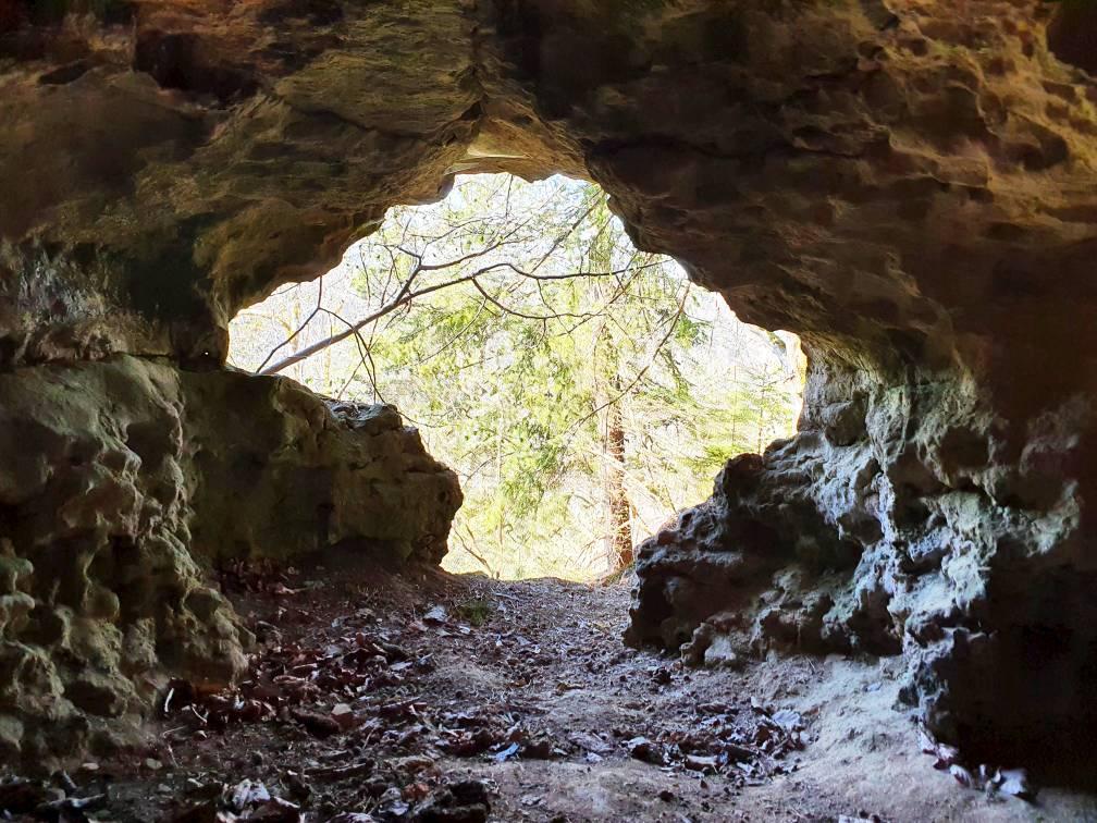 Höhleneingang mit strahlender Sonne und Grün