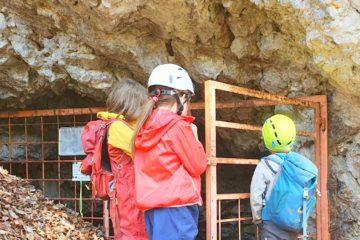 Kinder warten gespannt vor dem vergitterten Tor zur Höhle