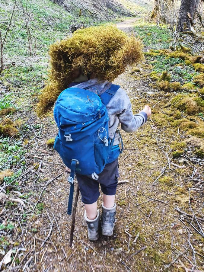 Ein Kind beim Wandern, gut mit Moos getarnt
