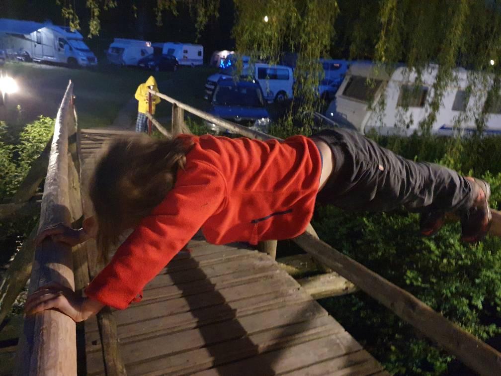 Ein Kind klettert am Brückengeländer