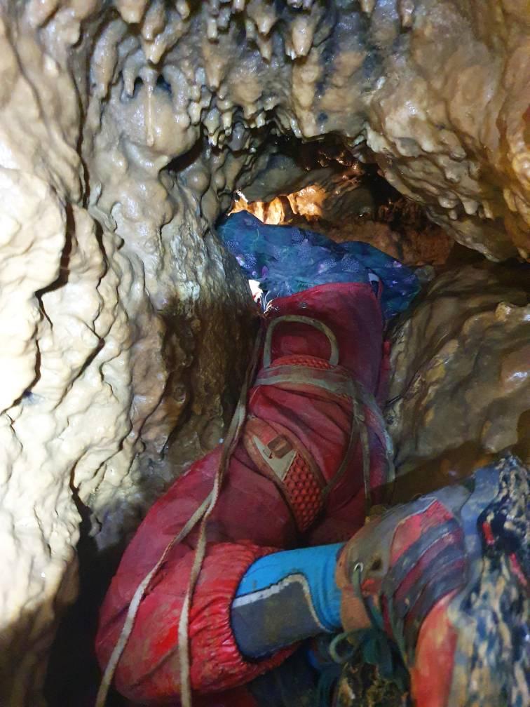 Ein Kind zwängt sich durch die engen Schlurfe der Beilsteinhöhle